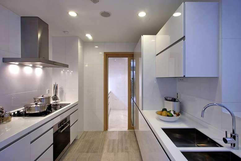 Mẫu tủ bếp song song với gam màu trắng chủ đạo và hệ thống chiếu sáng cho căn bếp